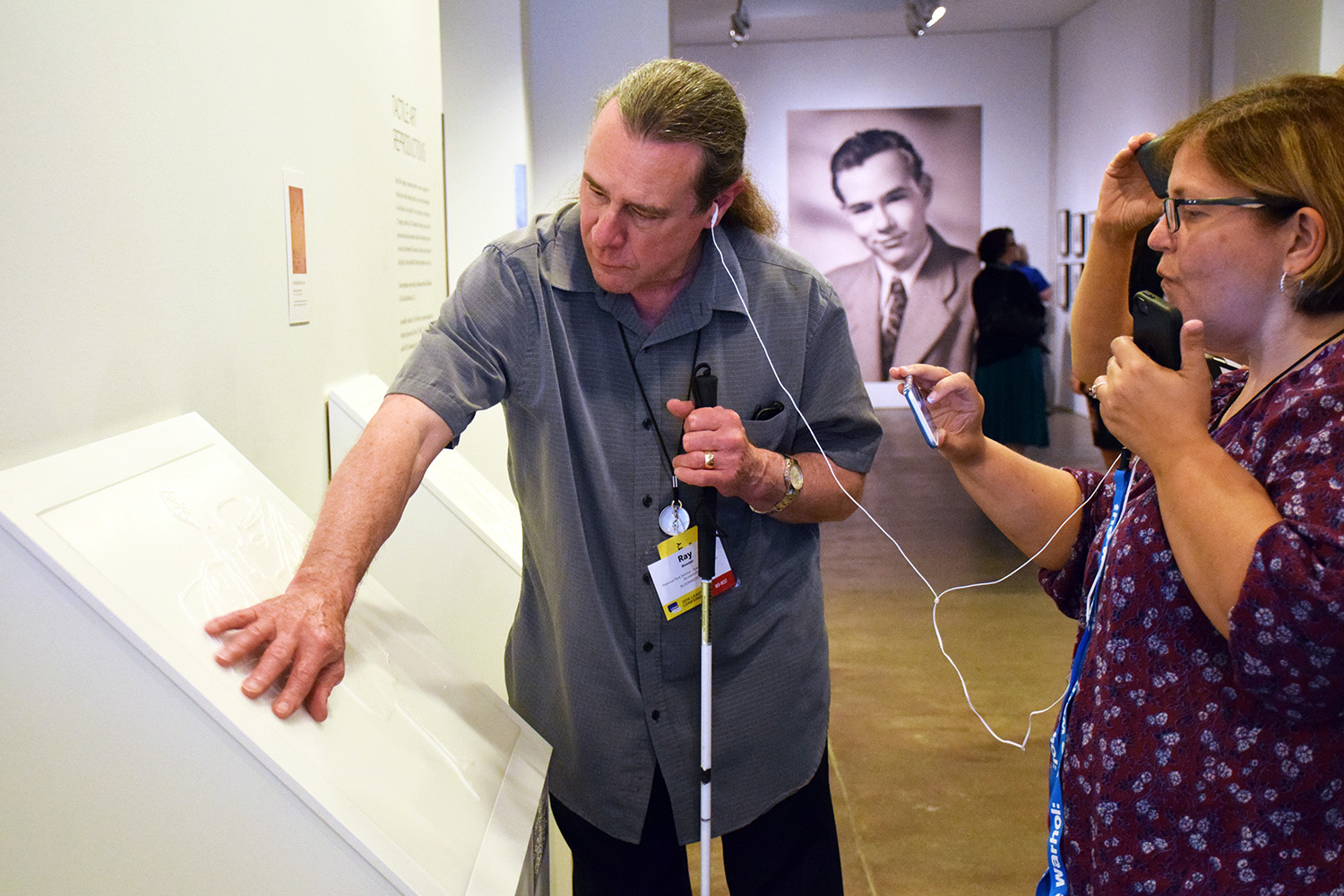 A man and a woman stand in the galleries of the Warhol, sharing an audio guide device. The man on the left holds a white cane in one hand and leans over to touch a white tactile reproduction with his other hand.