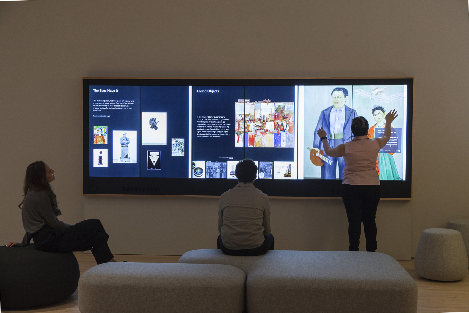 A photo inside SFMOMA's Painting an Sculpture Interpretive Gallery shows three visitors interacting with the Wall Experience. Two are seated on cushions while a third visitor uses both hands to interact with a large touch screen.