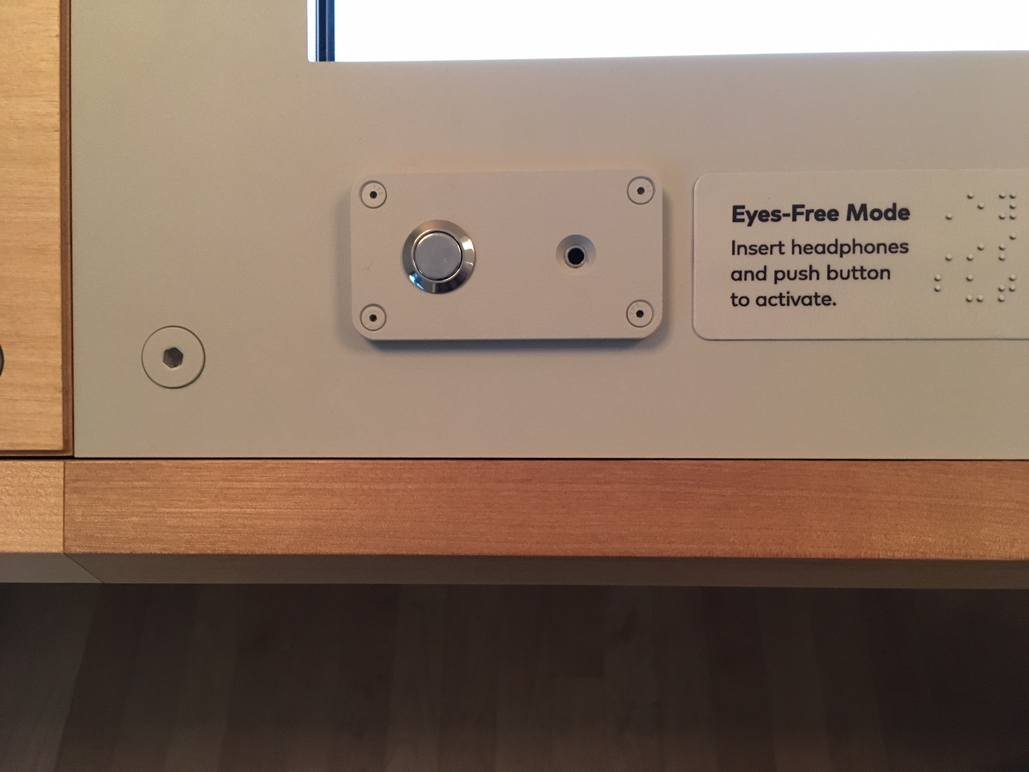 "A photo of the lower left corner of each station shows, from left to right, the push-button and headphone jack in a raised plate; the label ""Eyes-Free Mode. Insert headphones and push button to activate"" in SFMOMA's font and Braille."