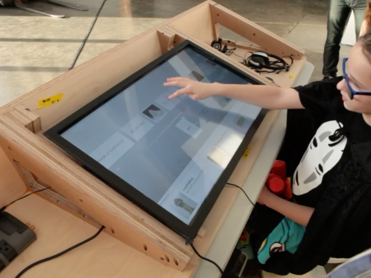 A young girl tests a prototype version of the Table Experience, placing her finger on a touchscreen mounted inside a wooden box.