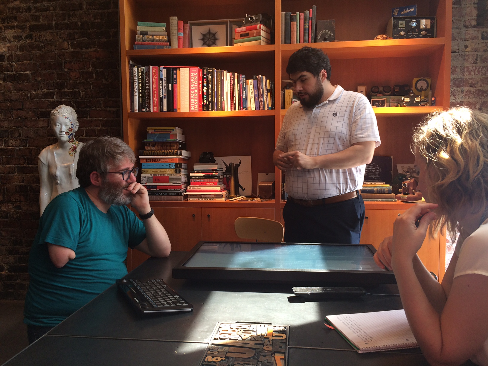 A photo inside the Belle & Wissell, Co. studio shows three individuals talking around a touch-screen laid on a conference table. From left to right are Shaun Kane, Sina Bahram, and Sarah Trueblood.