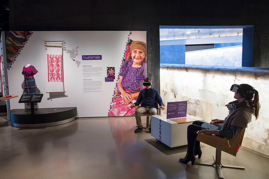 Guatemalan dress on display while 2 people with VR headsets sit in chairs.