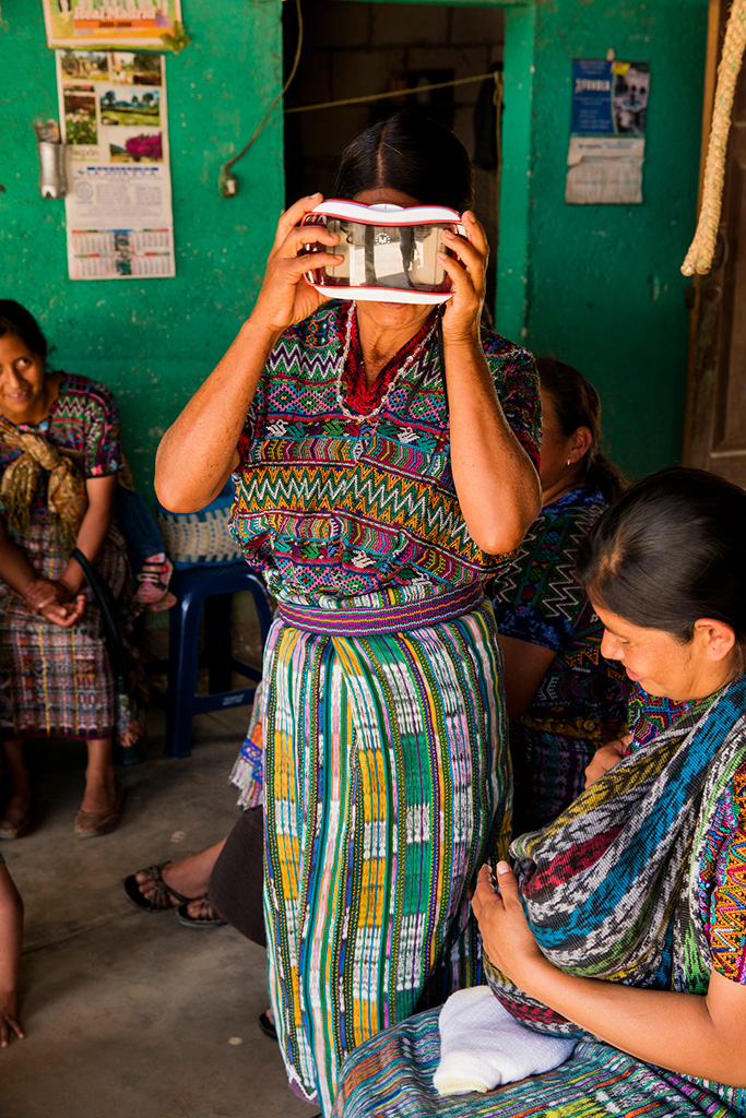 Guatemalan woman in traditional dress holding a virtual reality headset to her face while standing.